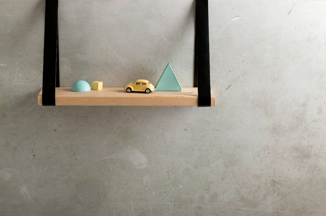 leather straps wooden decor shelf with miniature yellow bug car and pastel geometric shapes