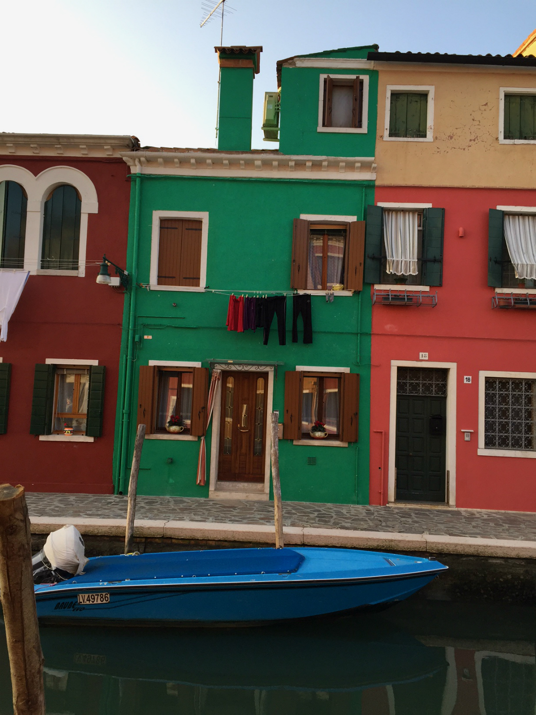 burano houses in green red and teracota by the canal