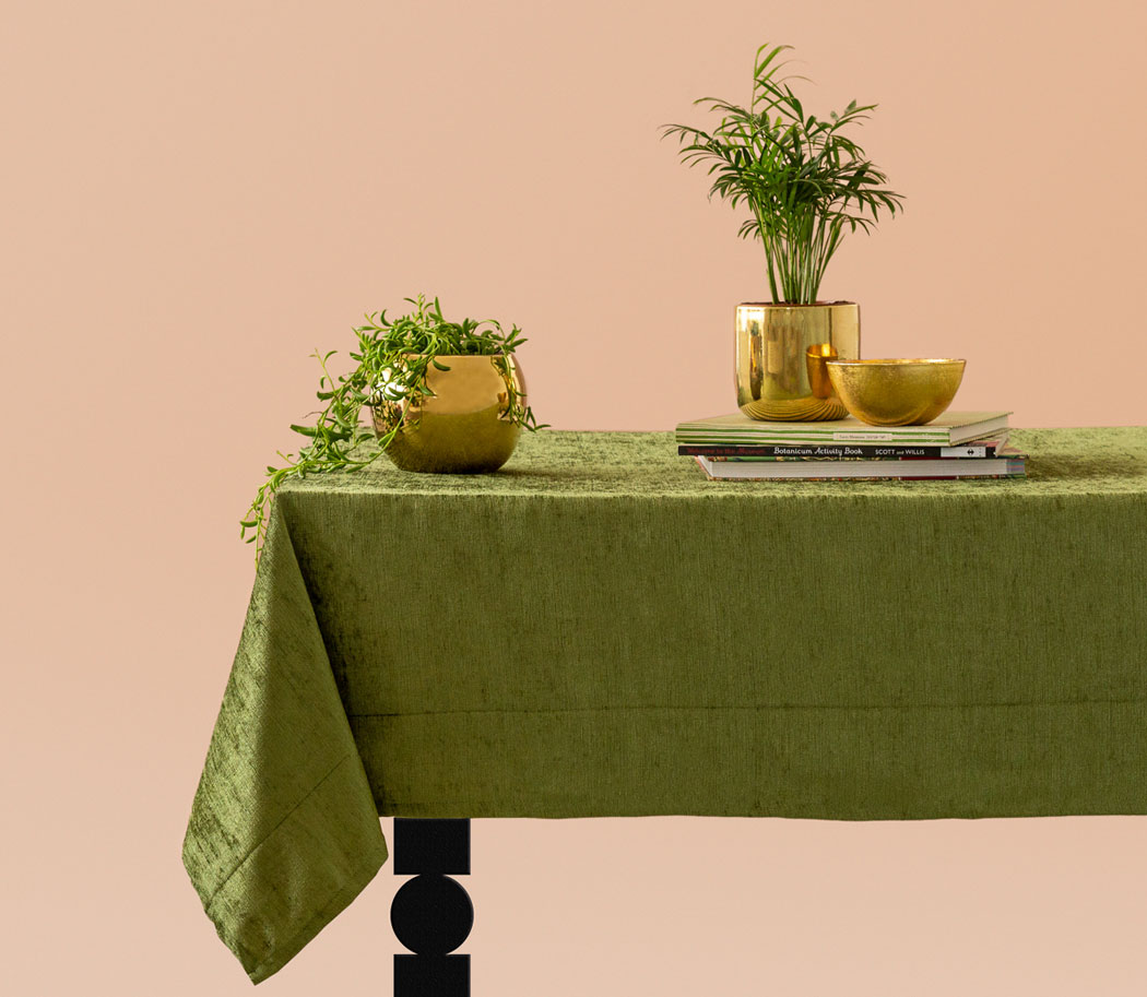 rich tablescape with velvet table cloth, gold brass flower plants and palm leaves