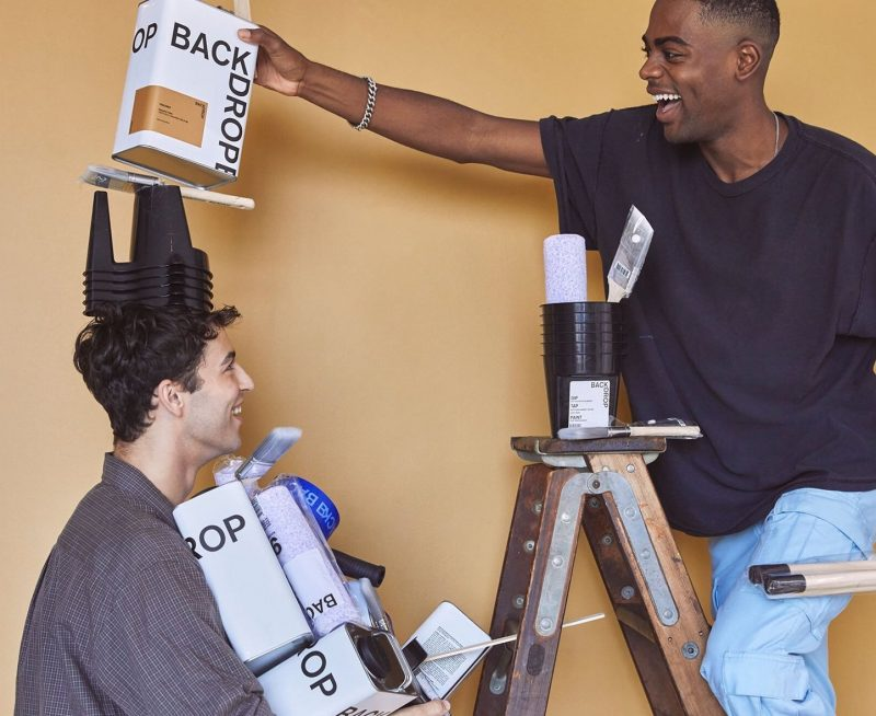 black man and white man having fun painting a wall in yellow